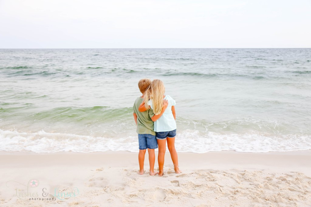 Brother and sister hugging each other and looking out at the water at Johnsons Beach in Perdido Key Florida