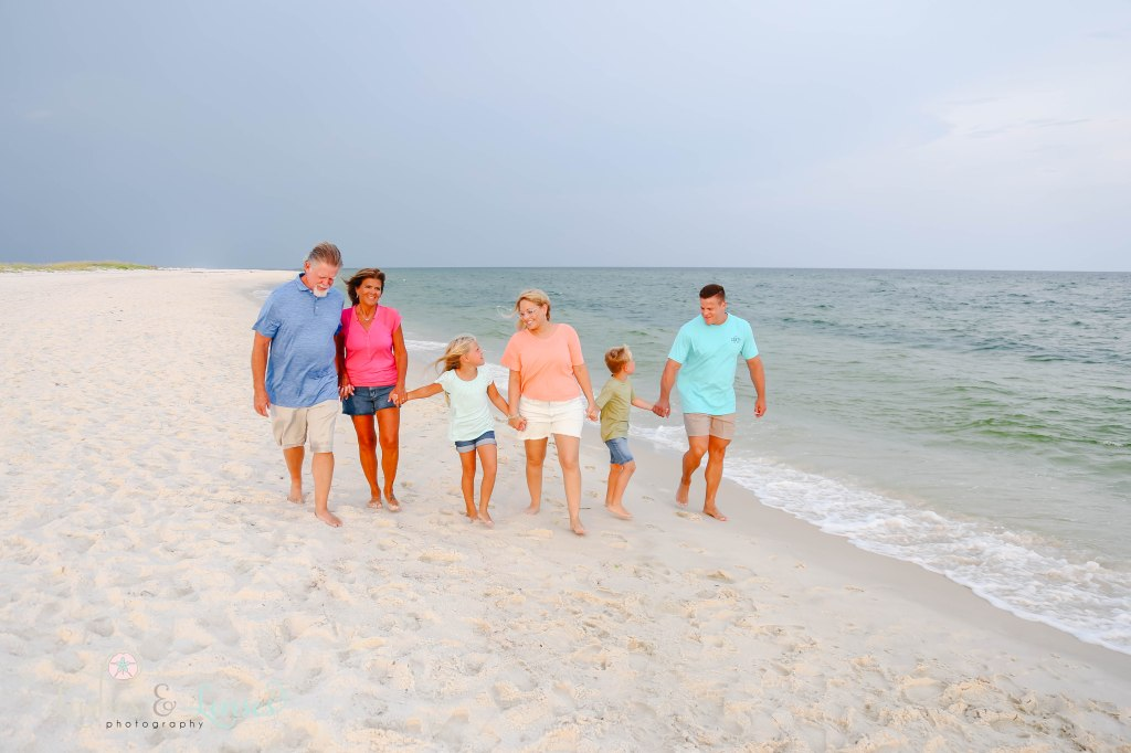 Grandparents, Mom and Dad and son and daughter walking down by the waters edge at Johnsons Beach in Perdido Key Florida