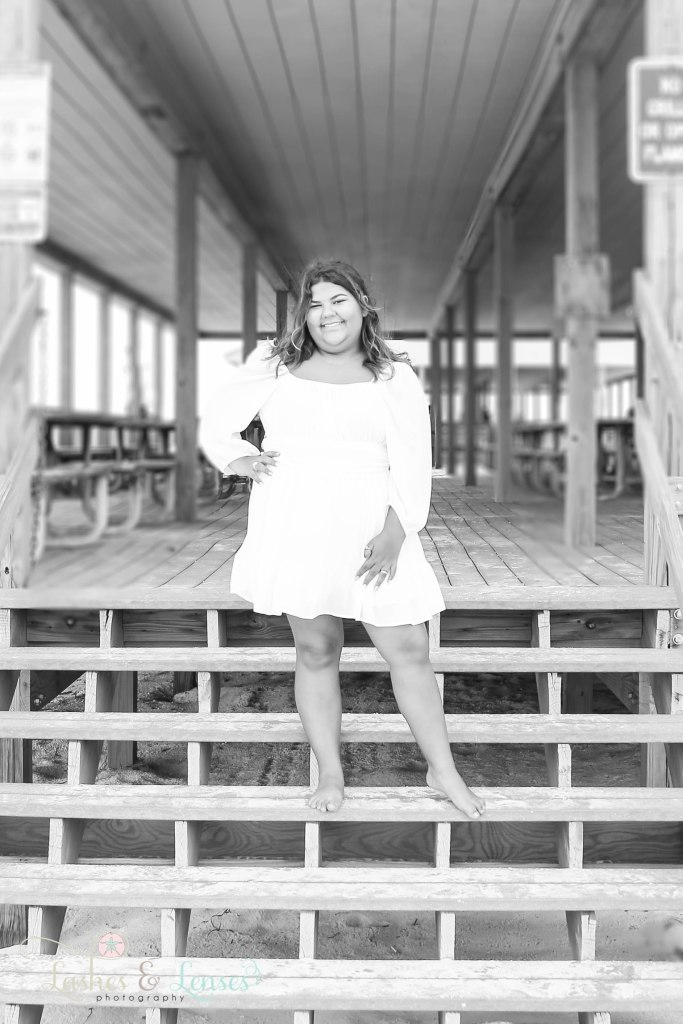 Black and White photo of Senior girl standing on the steps of a pavilion at Johnson's Beach in Perdido Key Florida
