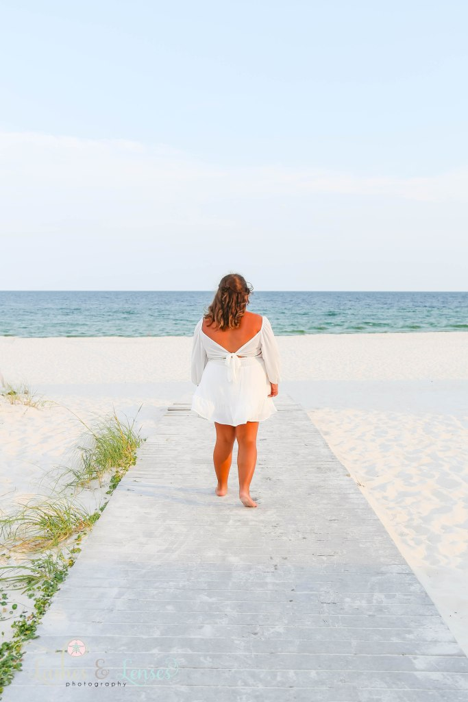 Senior girl walking down the boardwalk towards the water with her back to the camera at Johnson's Beach in Perdido Key Florida