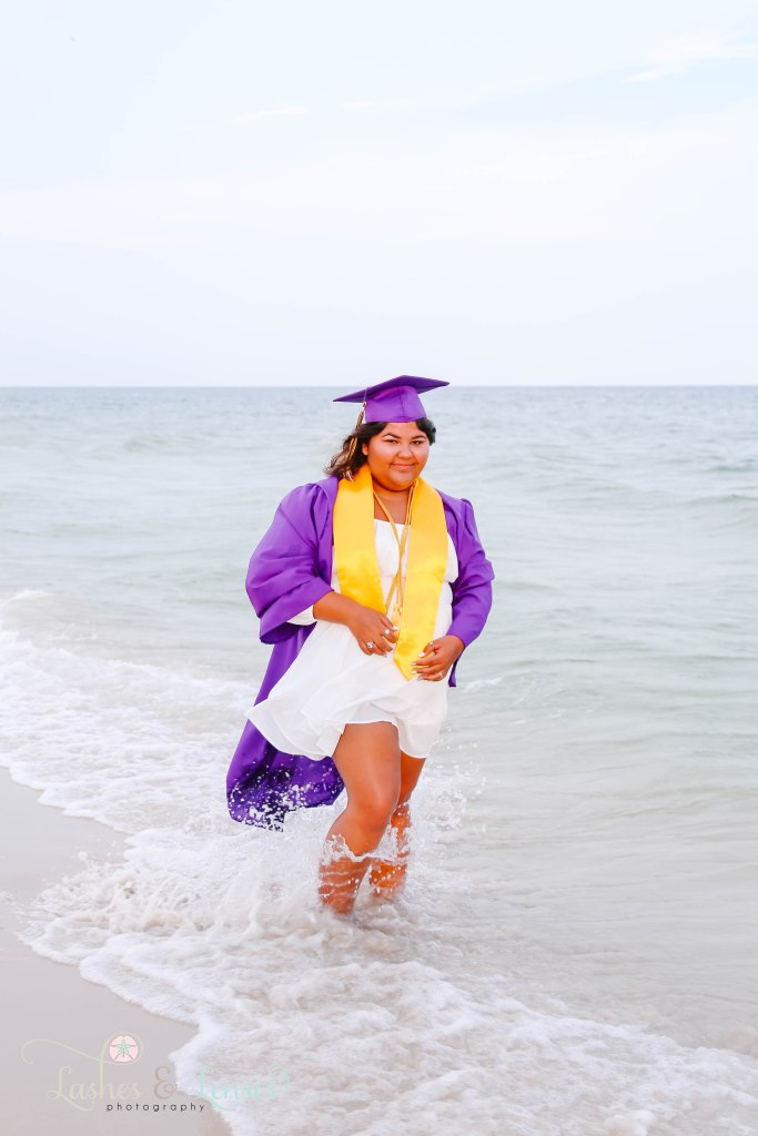 Senior girl wearing her cap and gown and standing in the water as the waves crash around her feet at Johnson's Beach in Perdido Key Florida
