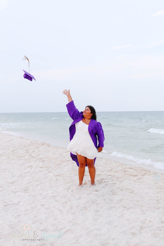 Senior girl throwing her cap in the air and standing next to the water at Johnson's Beach in Perdido Key Florida