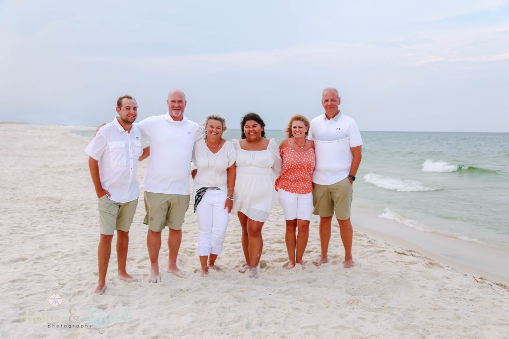 Two family of best friends all standing facing the camera with their hands on each others backs by the waters edge at Johnsons Beach in Perdido Key Florida