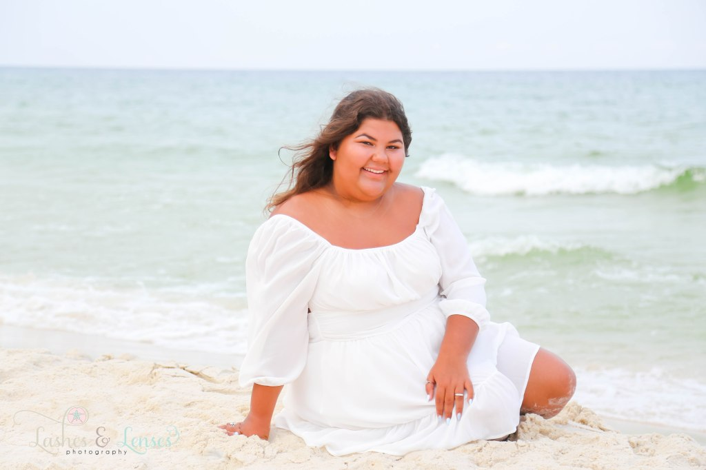 Senior girl sitting in the sand with the water behind her at Johnson's Beach in Perdido Key Florida