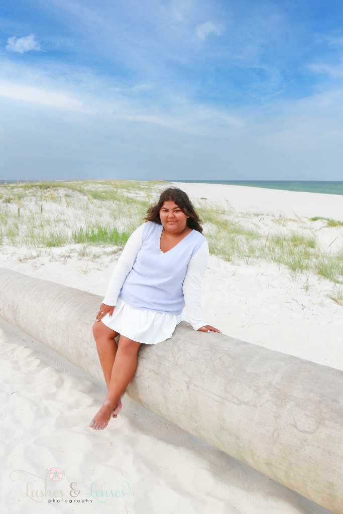 Senior girl sitting on a washed up palm tree at Johnson's Beach in Perdido Key Florida