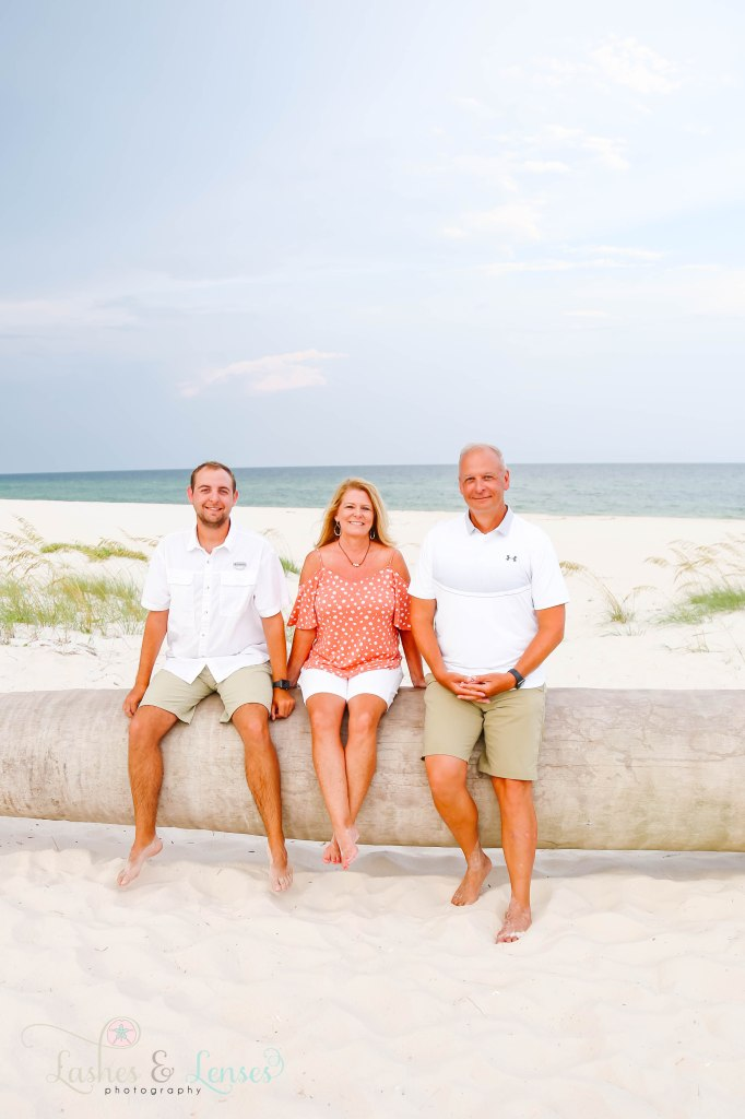 Young adult son and parents sitting on a washed up palm tree at Johnsons Beach in Perdido Key Florida