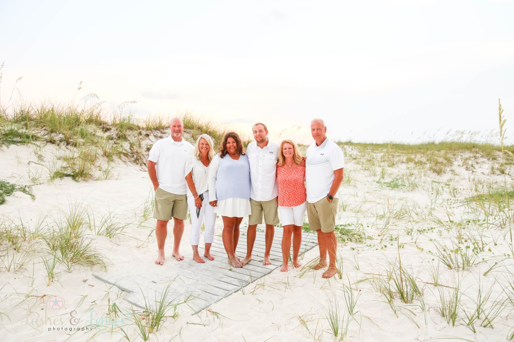 Two family of best friends all standing on a washed up boardwalk at Johnsons Beach in Perdido Key Florida