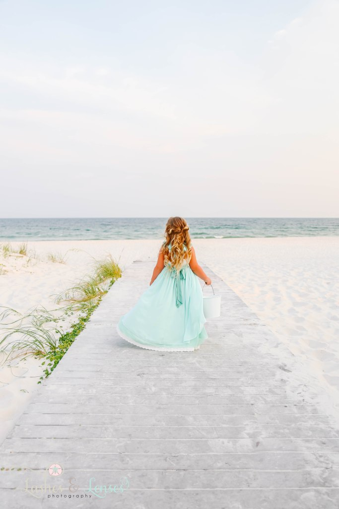 Little girl in long mint color dress walking down the boardwalk towards the water and holding a white sand bucket at Johnsons Beach in Perdido Key Florida