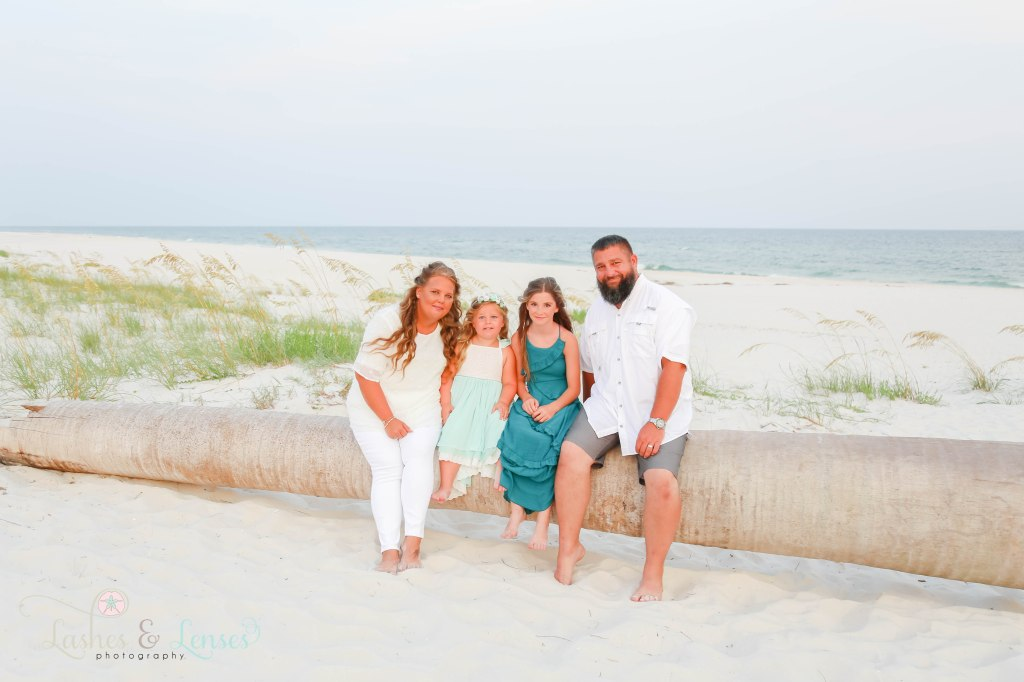 Mom, Dad, young daughter and teen girl friend sitting on washed up palm tree on the beach at Johnsons Beach in Perdido Key Florida