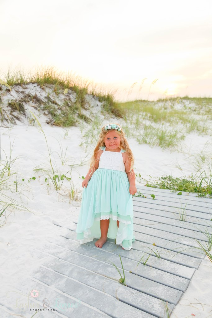 Little girl standing on a washed up boardwalk with the sand dunes and sea oats behind her at Johnsons Beach in Perdido Key Florida
