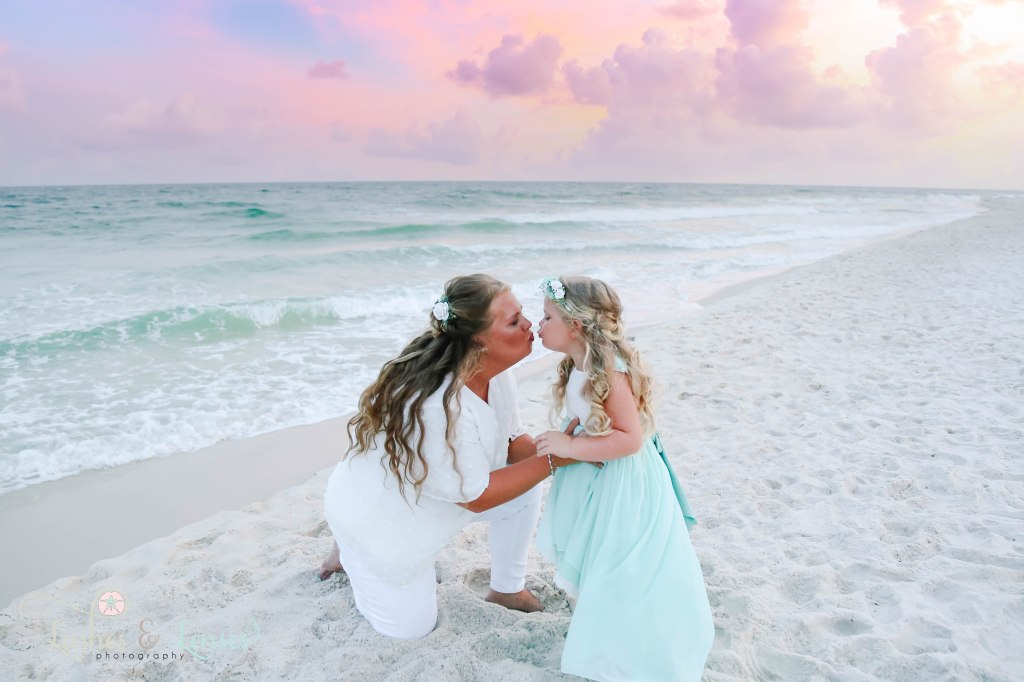 Mom kneeling down to kiss her daughter with the water behind them and a beautiful sunset at Johnsons Beach in Perdido Key Florida