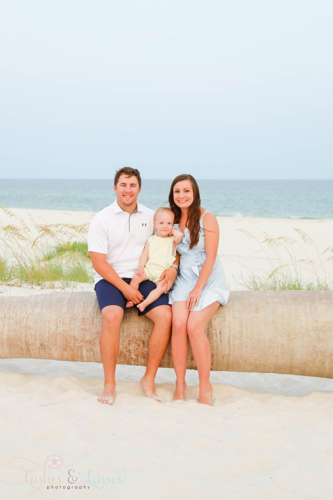 Mom and Dad sitting on a washed up palm tree with their year old son at Johnsons Beach in Perdido Key Florida