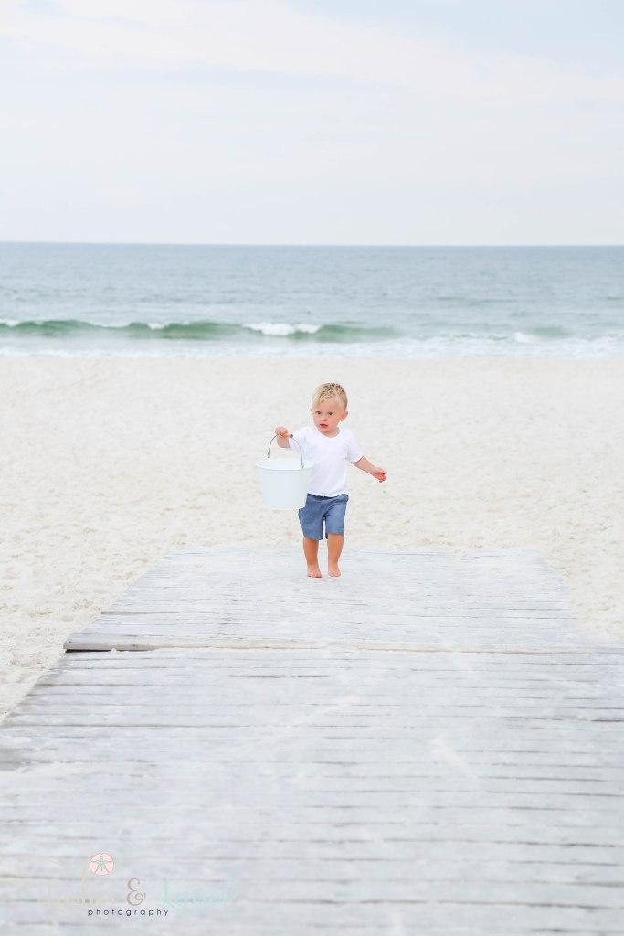Little Boy walking up boardwalk holding beach bucket with the water behind him at Johnsons Beach in Perdido Key Florida