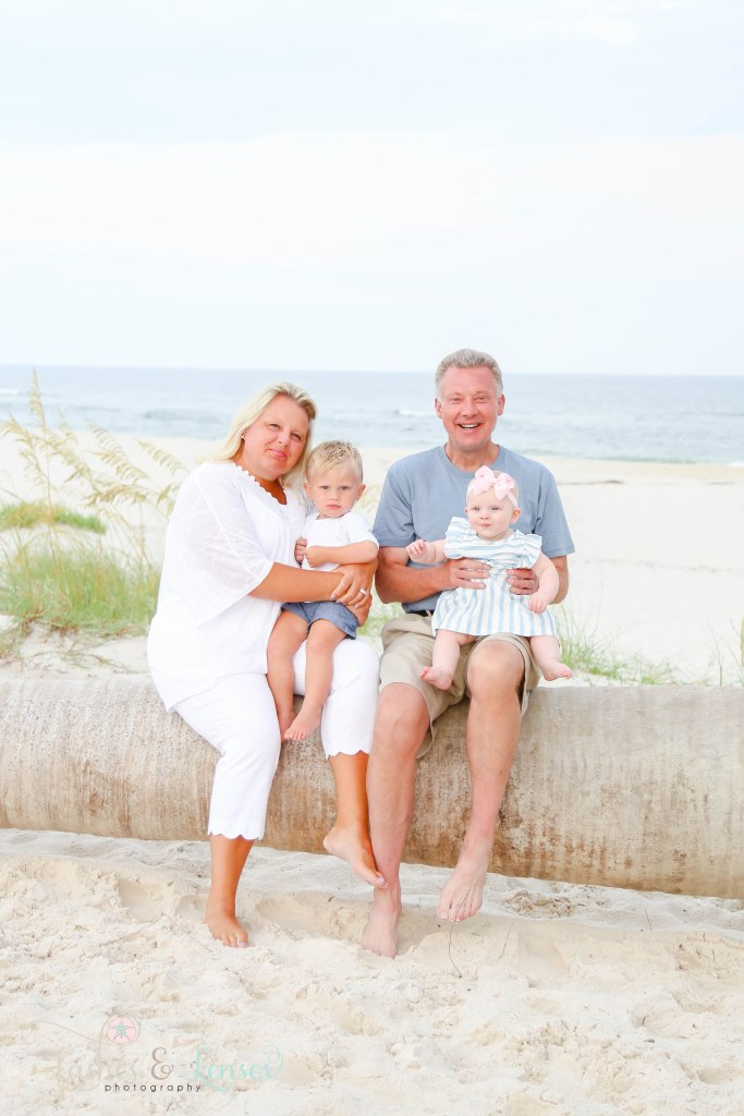 Paternal Grandma and Grandpa sitting on a washed up palm tree with their grandson and granddaughter at Johnsons Beach in Perdido Key Florida
