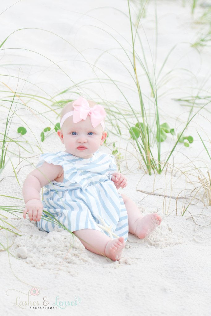 Baby girl sitting in the sand and playing with sea oats and a starfish at Johnsons Beach in Perdido Key Florida