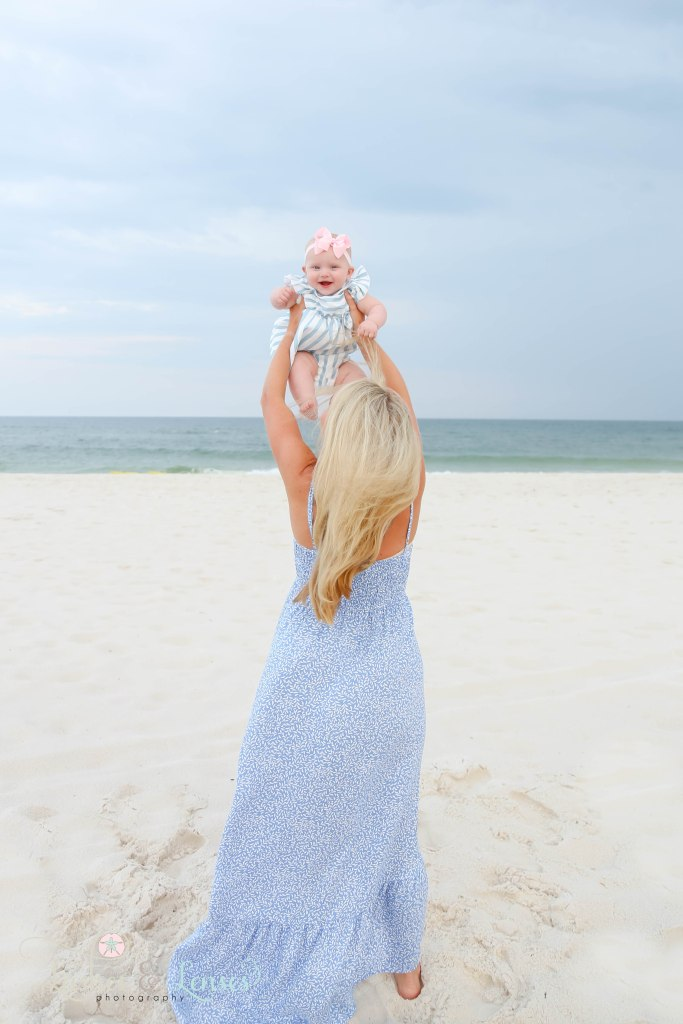Mama holding baby girl up in the air with the water behind them at Johnsons Beach in Perdido Key Florida