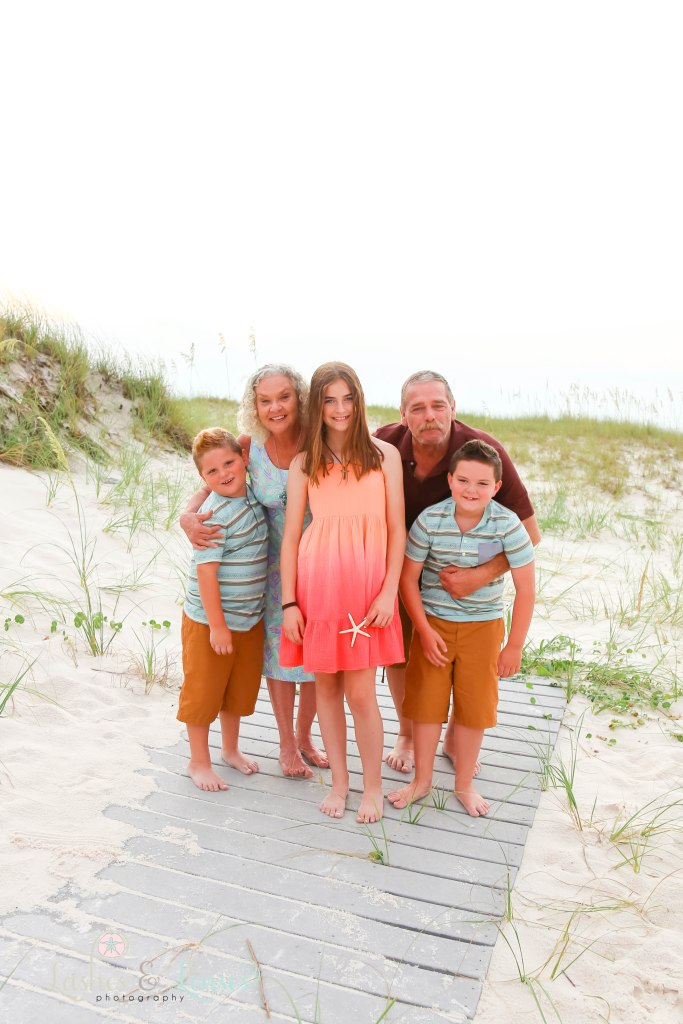 Grandma and Grandpa with their two grandsons and granddaughter standing on a washed up boardwalk at Johnsons Beach in Perdido Key Florida
