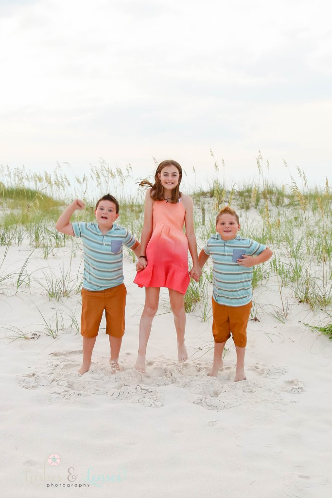 Cousins jumping in the air with the sand dunes behind them at Johnsons Beach in Perdido Key Florida