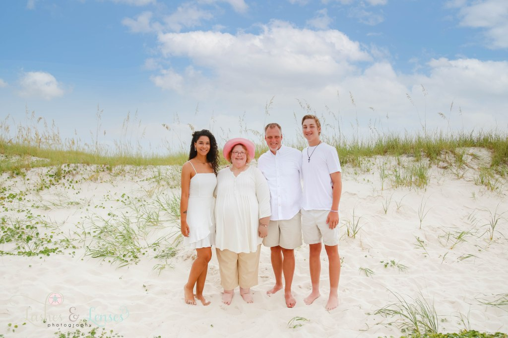 Mom and Dad with their young adult son and daughter, standing by the san dunes at Johnsons Beach in Perdido Key Florida