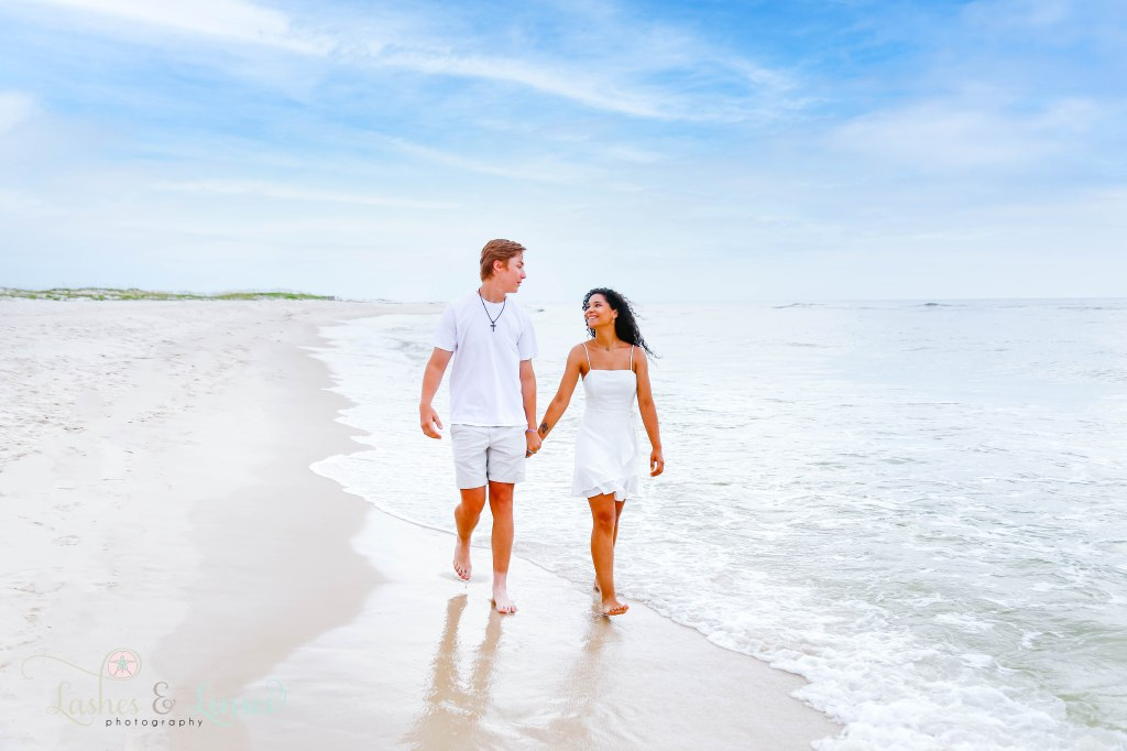 Young adult brother and sister holding hands and walking along the waters edge at Johnsons Beach in Perdido Key Florida
