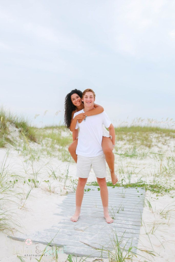 Adult sister on brothers back and standing on a washed up boardwalk at Johnsons Beach in Perdido Key Florida