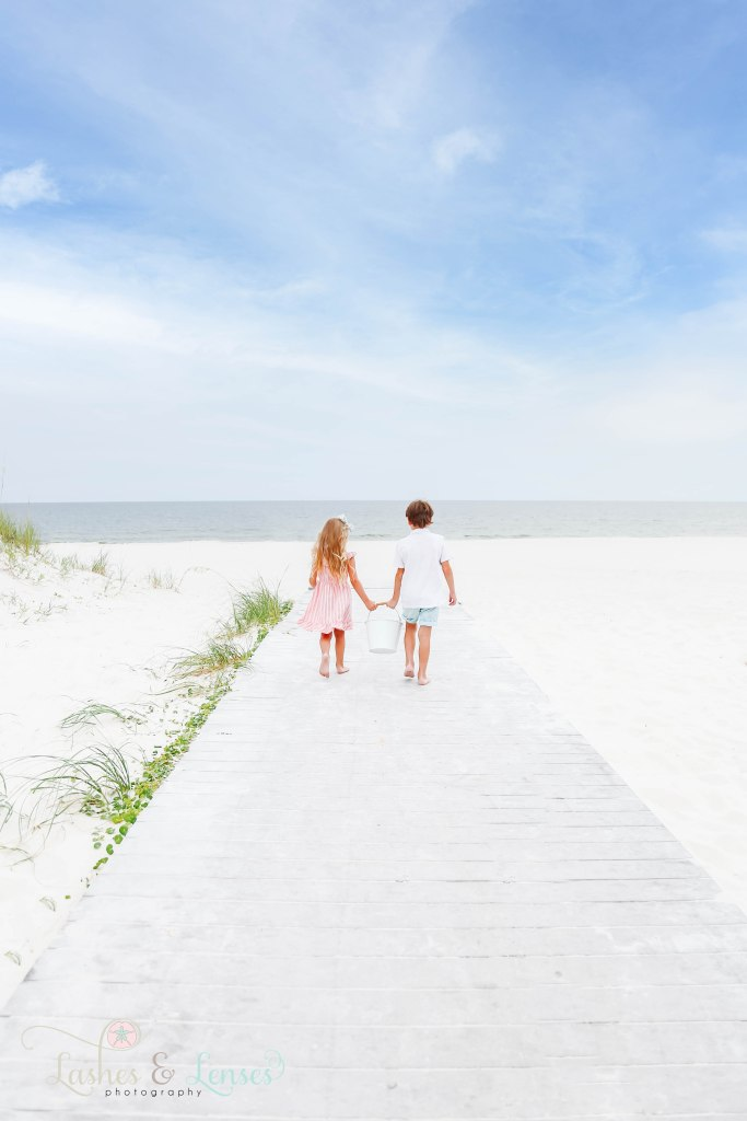 Young brother and sister walking down the boardwalk and holding a bucket at Johnsons Beach in Perdido Key Florida