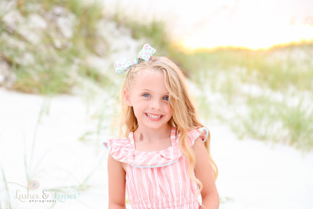Close up photo of little girl in pink and white stripped dress at Johnsons Beach in Perdido Key Florida