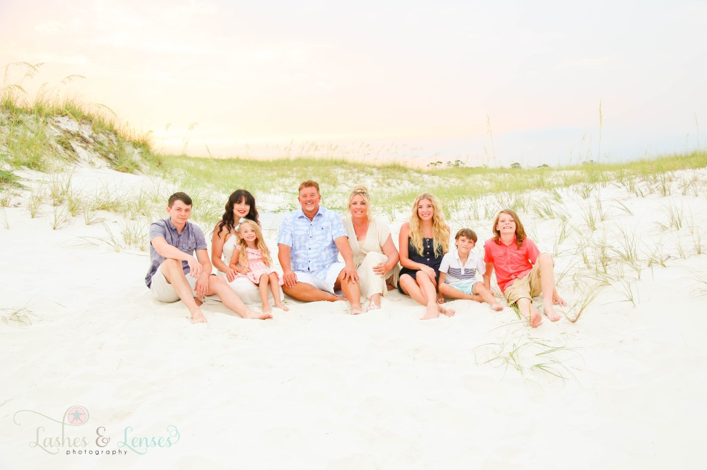 Extended family sitting in the sand Witt he sand dunes and sea oats behind them at Johnsons Beach in Perdido Key Florida