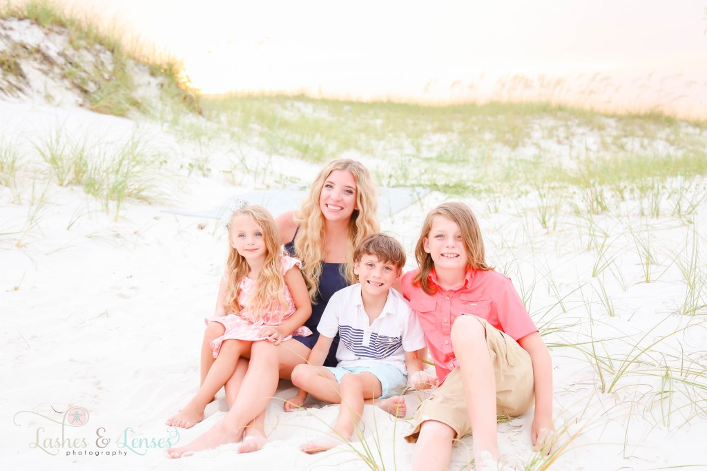 Mom sitting in the sand with her two sons and her daughter with the sand dunes behind them at Johnsons Beach in Perdido Key Florida