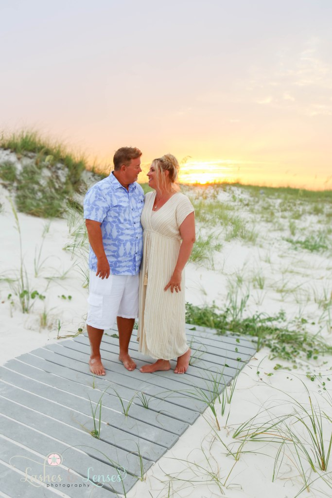 Husband and wife standing on a washed up boardwalk and looking at each other at Johnsons Beach in Perdido Key Florida