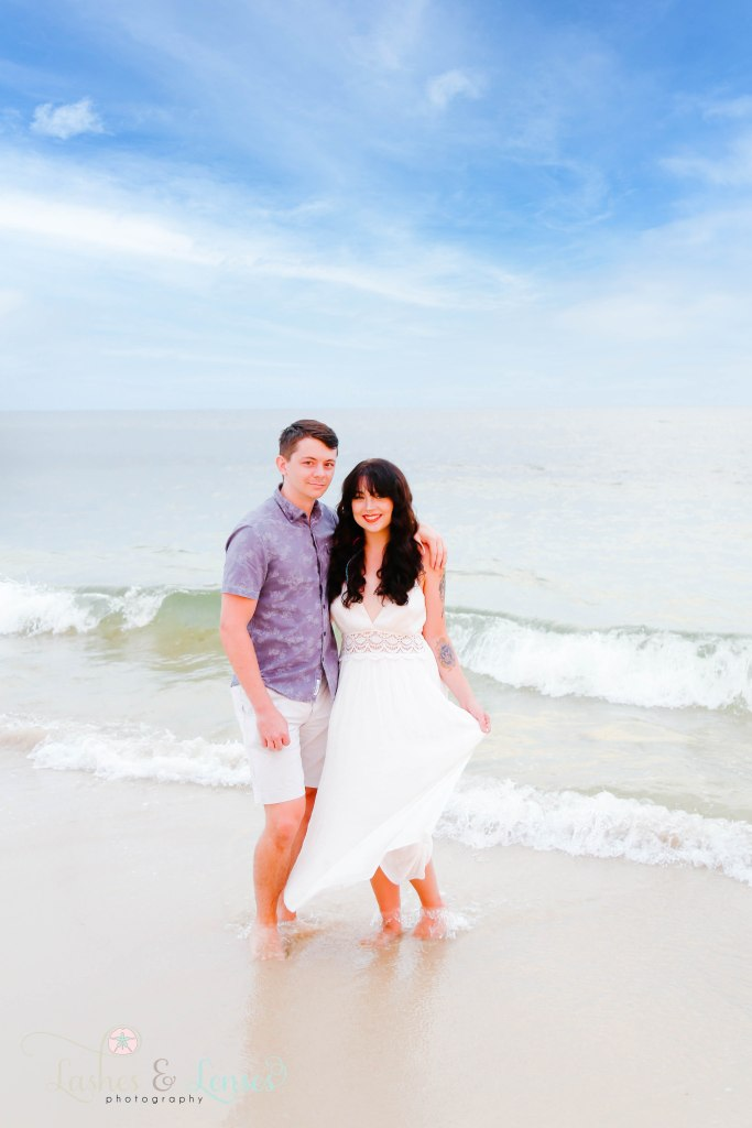 Young couple standing down by the waters edge at Johnsons Beach in Perdido Key Florida