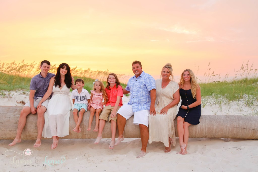 Extended family sitting on a washed up palm tree with the sun set behind them at Johnsons Beach in Perdido Key Florida