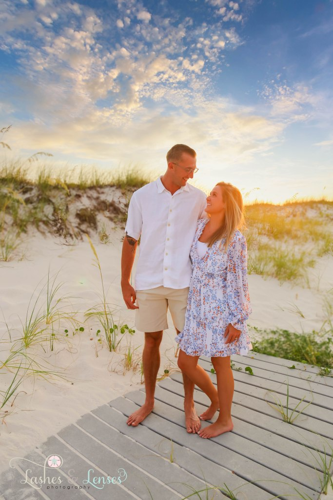 Young couple looking at each other and standing on a washed up boardwalk with the sea oats behind them at Johnsons Beach in Perdido Key Florida