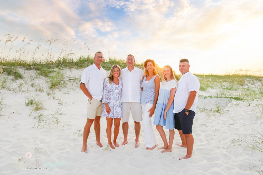 Mom and Dad with their children and spouses with the sunset behind them at Johnsons Beach in Perdido Key Florida