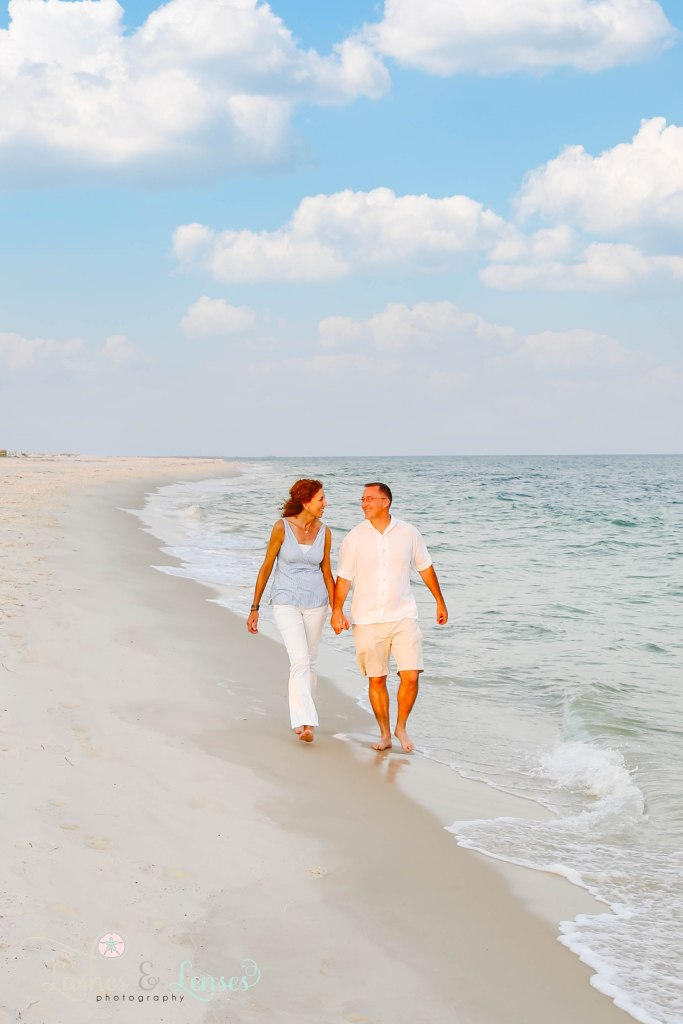 Husband and wife holding hands and walking along the waters edge at Johnsons Beach in Perdido Key Florida