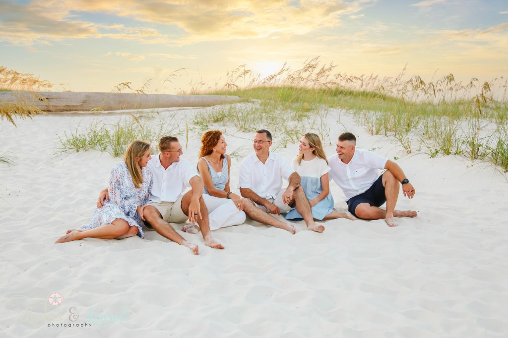 Family with two sets of children and their spouses sitting in the sand with the sunset behind them at Johnsons Beach in Perdido Key Florida