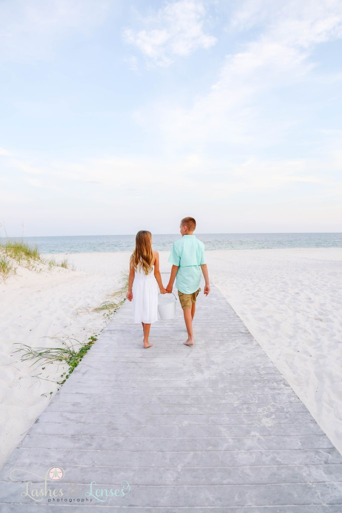 Brother and Sister walking down the boardwalk towards the water and holding a sand bucket at Johnsons Beach in Perdido Key Florida