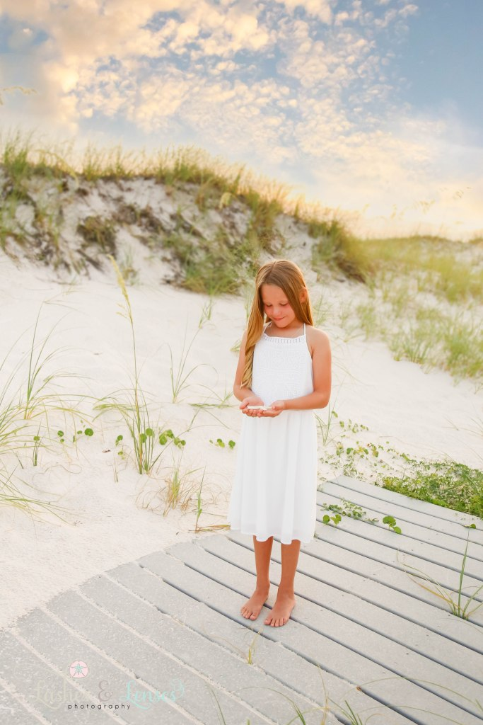 Little girl holding starfish and looking down at it with the sunset behind them at Johnsons Beach in Perdido Key Florida