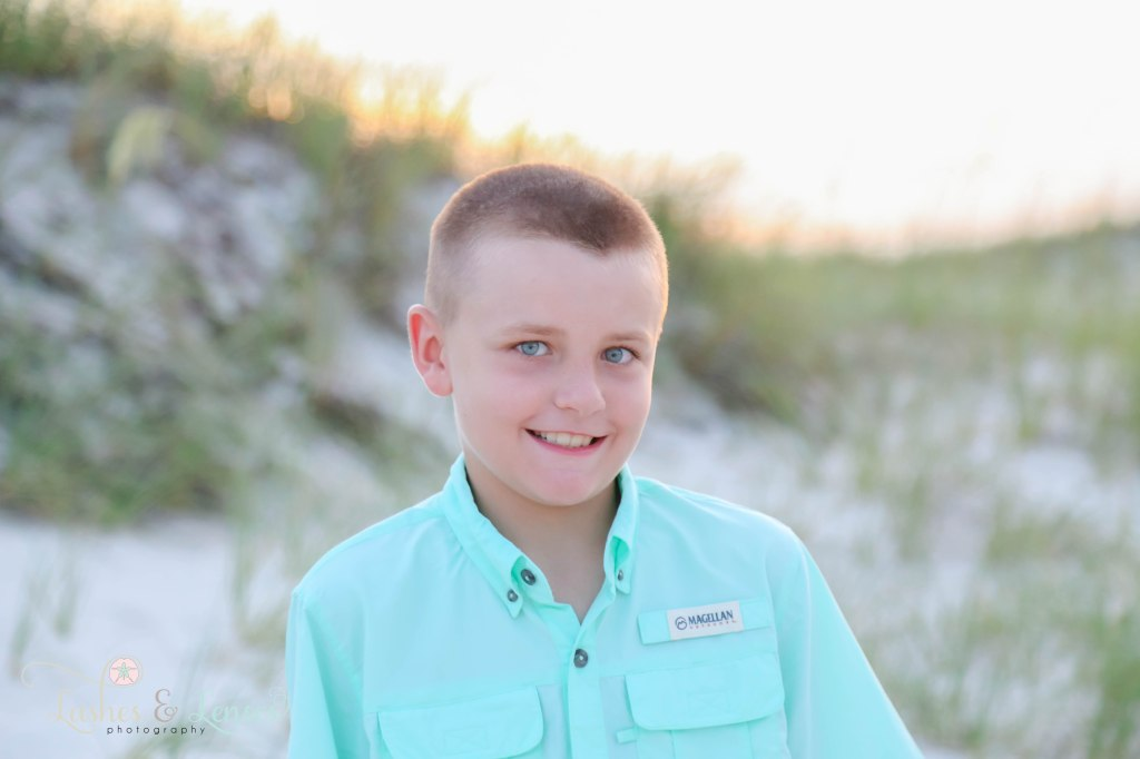 Close up photo of an elementary boy with the sea oats behind them at Johnsons Beach in Perdido Key Florida