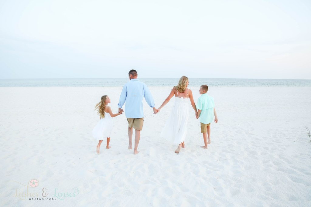 Family of four holding hands and walking towards the water at Johnsons Beach in Perdido Key Florida