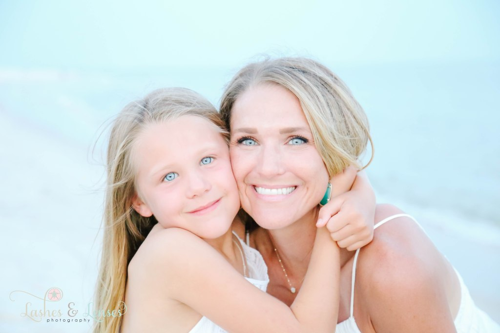 Close up photo of Mom and daughter with the water behind them at Johnsons Beach in Perdido Key Florida