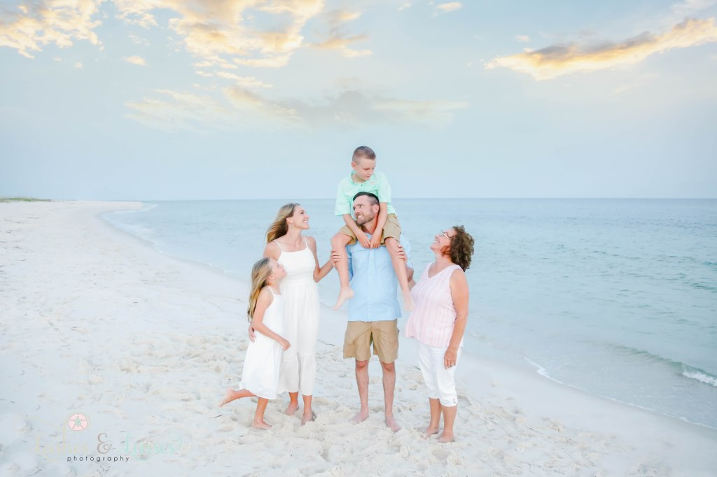Mom and Dad looking at each other, son on dads shoulders and looking down at grandma and daughter looking up at brother at Johnsons Beach in Perdido Key Florida