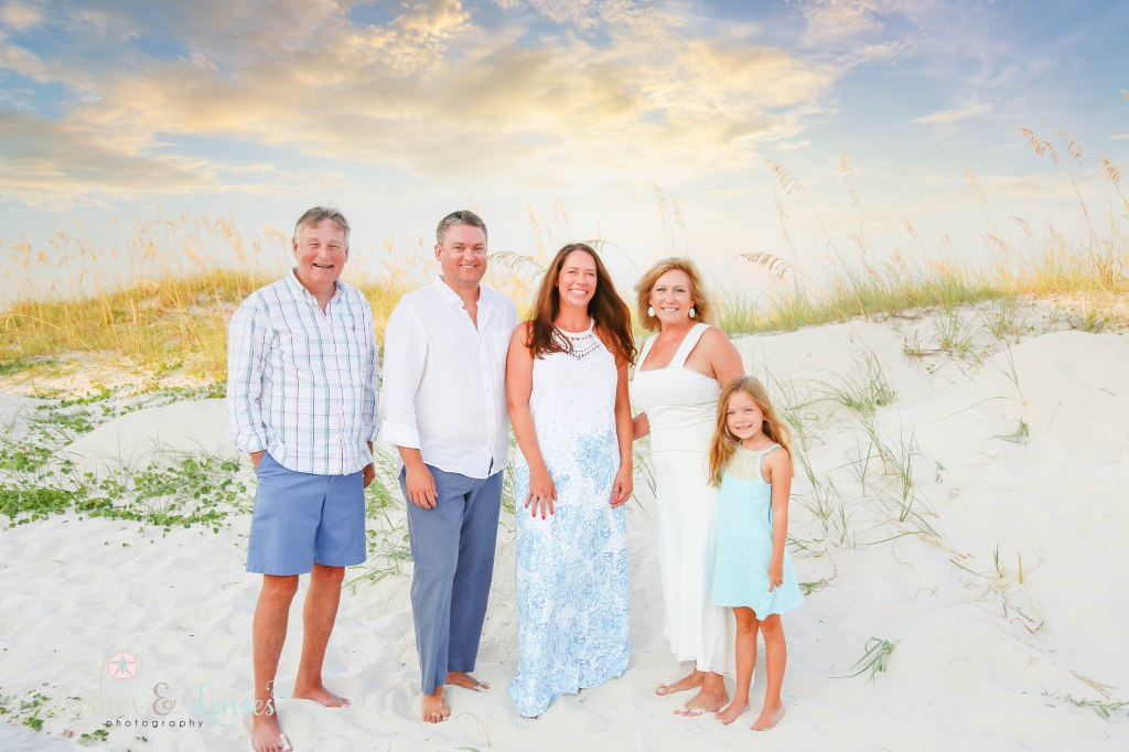 Grandparents, Mom and Dad and young daughter standing with their backs to the sand dunes and sea oats at Johnsons Beach in Perdido Key Florida