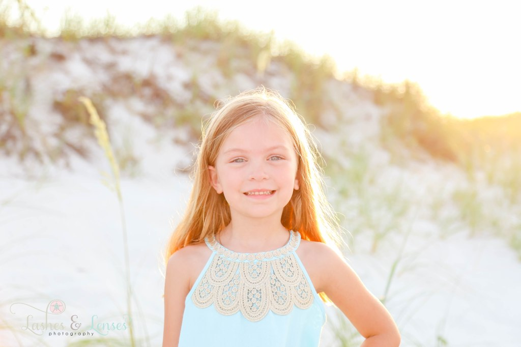 Close up photo of young girl with the sand dunes behind her at Johnsons Beach in Perdido Key Florida