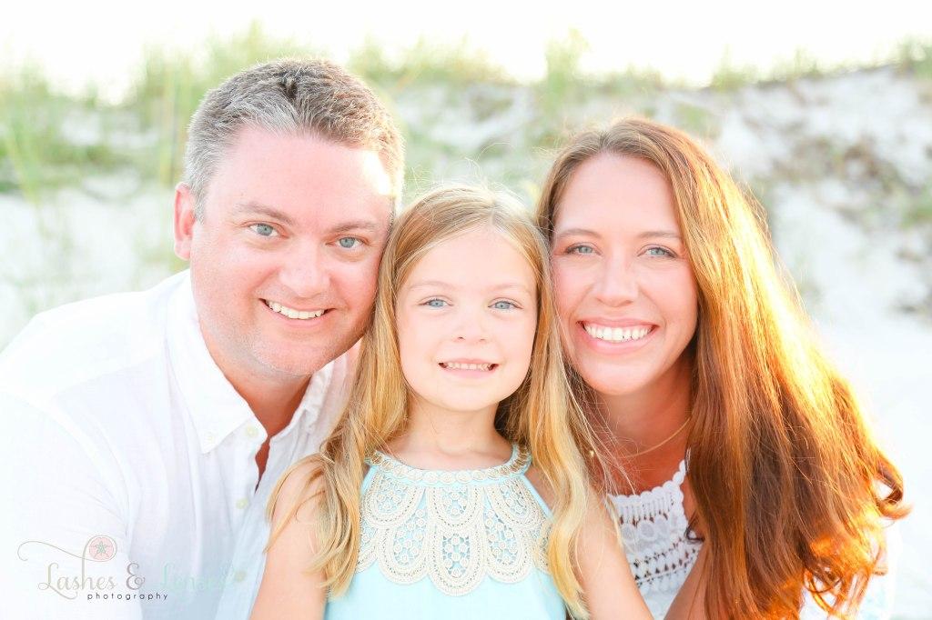 Close up photo of mom and dad hugging daughter close and smiling and looking right at the camera at Johnsons Beach in Perdido Key Florida