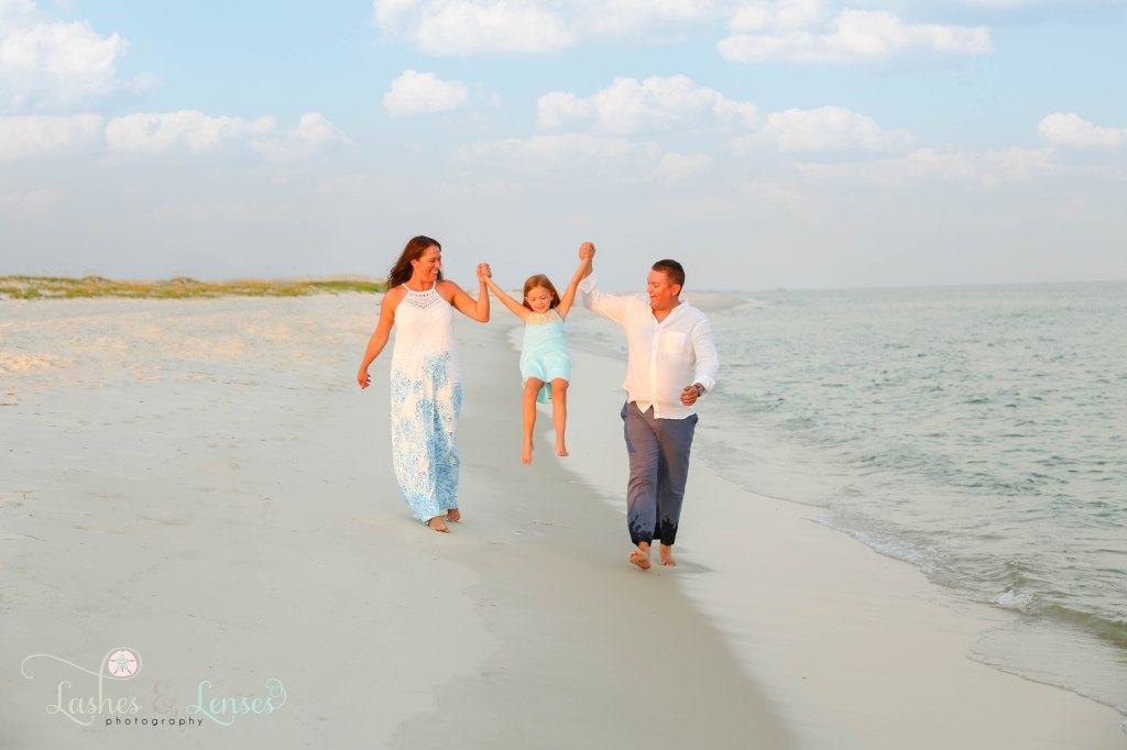 Mom and Dad walking by the edge of the water and swinging their daughter in between them at Johnsons Beach in Perdido Key Florida