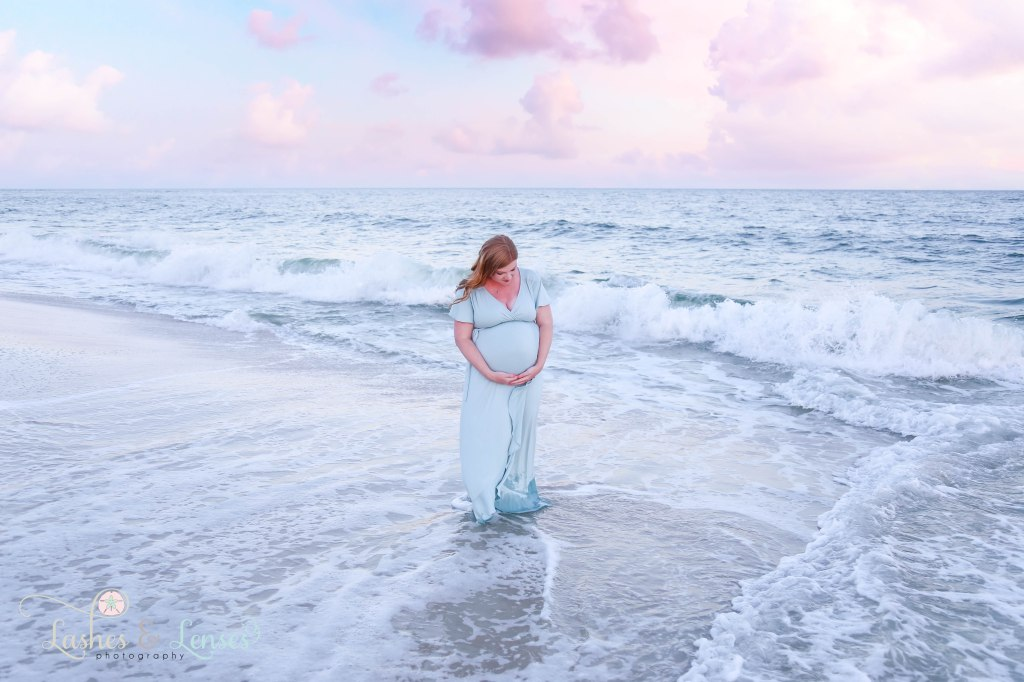 Pregnant Woman holding her belly and looking down at her belly and standing in the waves with the sunset behind her at Johnsons Beach in Perdido Key Florida