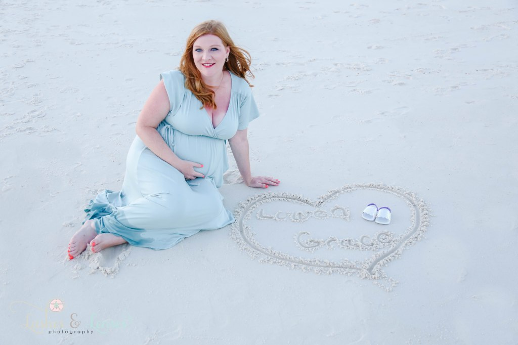 Pregnant Woman sitting in the sand with her baby name wrote in the sand at Johnsons Beach in Perdido Key Florida