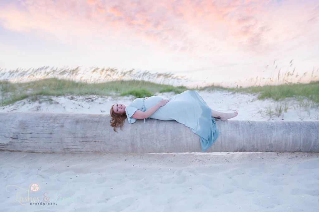 Pregnant Woman laying on a washed up palm tree and highlighting her belly with the sunset behind her at Johnsons Beach in Perdido Key Florida