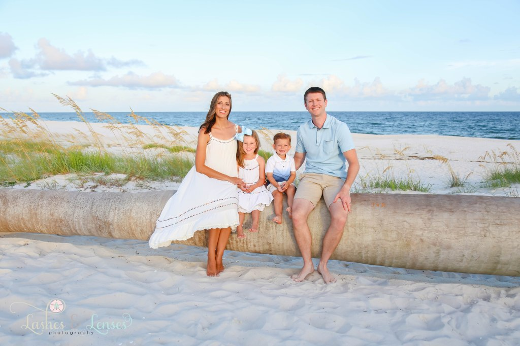 Mom, Dad, young daughter and toddler son sitting on a washed up palm tree with the water behind them at Johnsons Beach in Perdido Key Florida